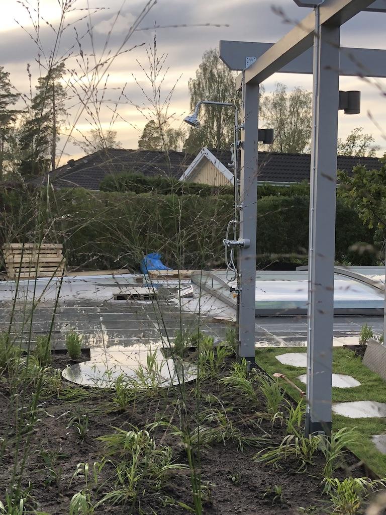 Prydnadsgräs, pergola och trampstenar till pooldäck